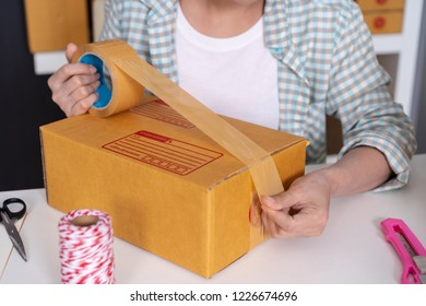 close up hand of woman online entrepreneur using tape to packing parcel box at home office, prepare product for deliver to customer.
