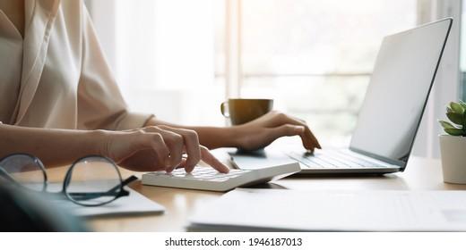 Nahaufnahme der Hand von Frau, die Computer-Berechnung Haushaltsfinanzen oder Steuern auf Maschine, Frauen verwalten Haushalt Familienausgaben, mit dem Rechner, machen Zahlung auf Laptop-Laptop