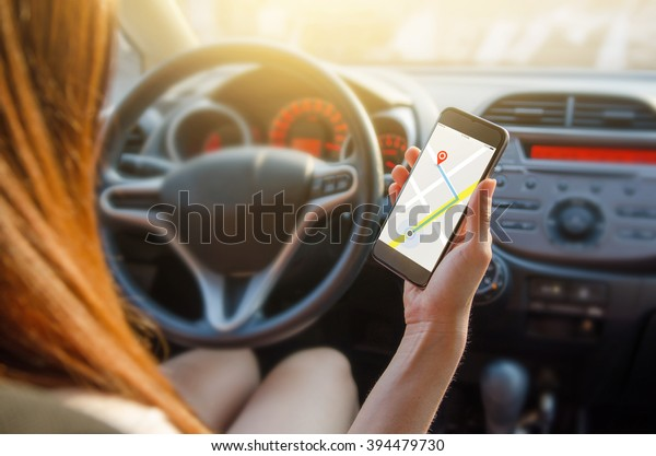 Close up hand woman using navigation or gps on mobile smartphone. Blurred car interior background. Viewing location map in network via smartphone during road trip