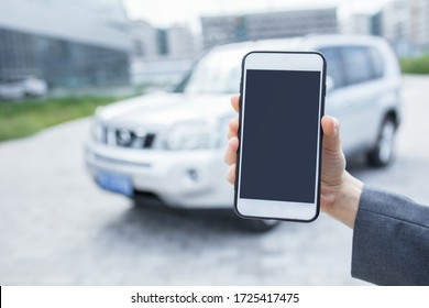 Close up hand of woman using smartphone and blur of her broken car parking on the road. Contacting car technician or need help concept