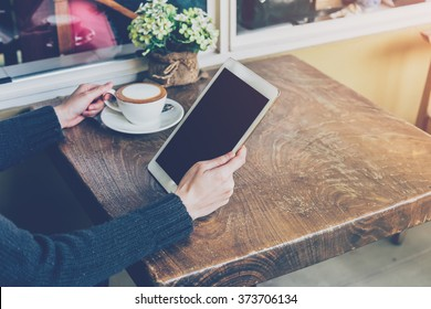 Close up hand woman using tablet in coffee shop with vintage tone.