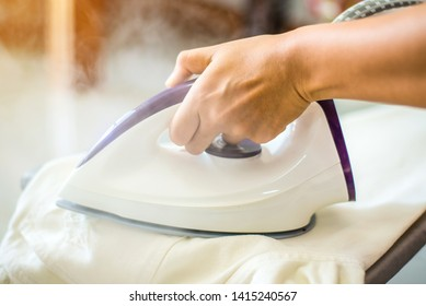 Close up hand of women ironing shirt on the table. Household duties, housework and housekeeping concept
