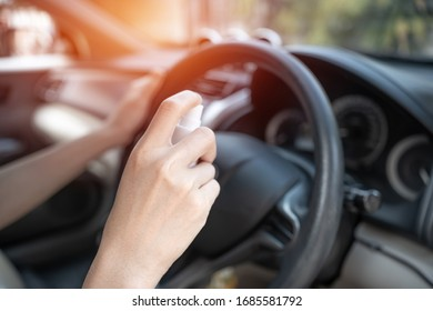 Close up hand women use Alcohol spray clean steering wheel and inside car part cleaning concept with virus in transport
