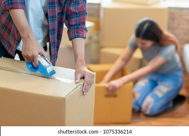 Close up hand of young man and his couple using tape packing their belonging before move to new resident.