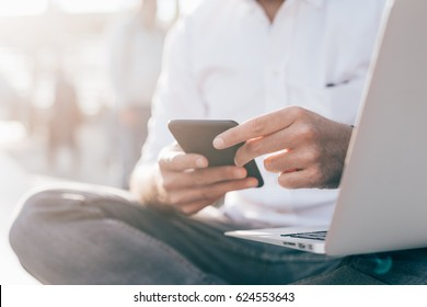 close up hand of young man holding smart phone and using computer - business, social network, multitasking concept