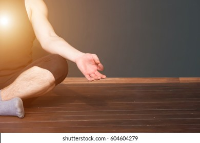 Close up of hand of young man sitting in lotus pose indoor. Light, zen and home yoga exercising concept with copyspace. Healthy lifestyle concept.