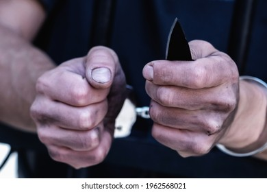 Close up handcuffed man with a knife imprisoned for crime, punished for serious villainy. Arrest, gangster, pain concept. Selective focus.