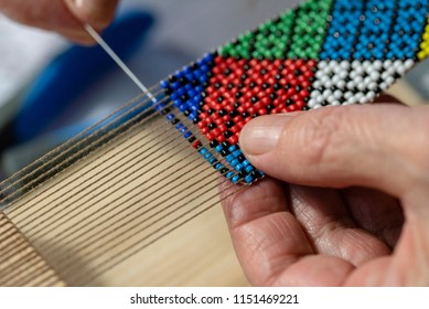 A close up of a handmade beaded jewelry on a loom with with hands beading a colourfull pattern with a needle on a loom with a blurry background.