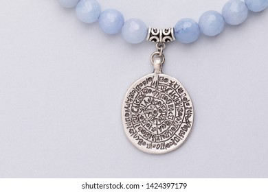 Close up of handmade necklace with pendant with copy space, studio photography on light gray background negative space. Blue candy jade beaded jewelry, necklace, steel pendant engraved with symbols.