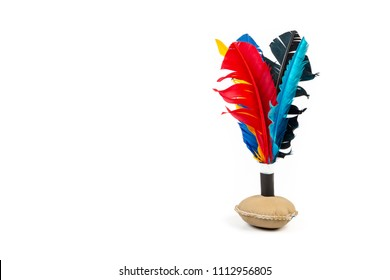 Close up of handmade shuttlecock toy with colourful feathers on white background.