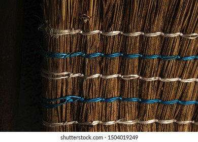 A close up of a handmade traditional broom, made from wattle/dry branches and wood. The broom wattles are tied with blue and white rope. Texture/broom/close up.