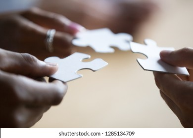 Close up hands of african american and caucasian associates multinational teammates holding white pieces of puzzle, people searching and finding solution. Team building, teamwork and support concept