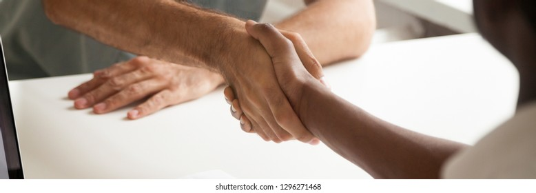 Close up hands of african and caucasian male shake hands express respect, greeting farewell symbol, boss meets client, successful negotiations concept, horizontal photo banner website header design
