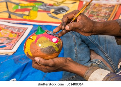 Close up of the hands of a artist painting colorful earthen pot piggy bank.