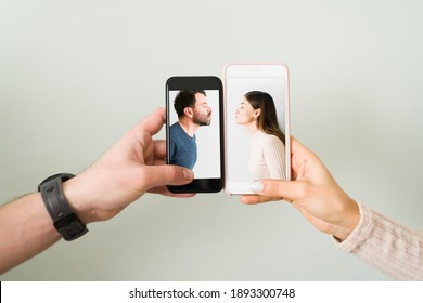 Close up of the hands of an attractive couple with smartphones and the photograph of a latin young woman and man in love and kissing. Love concept