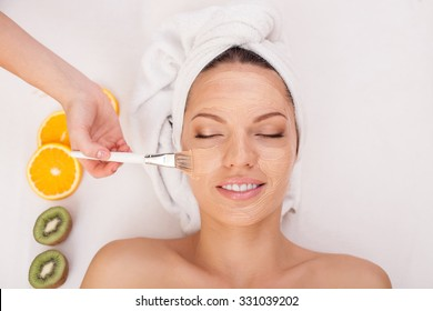 Close up of hands of beautician applying clay cosmetic mask on female face. The woman is lying and smiling at spa. She closed eyes with pleasure