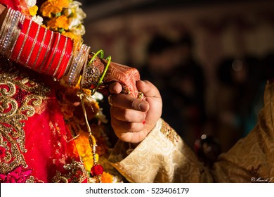 Close up of hands of bride and groom. A close up of hands of a groom holding his bride's hands at an Indian wedding.