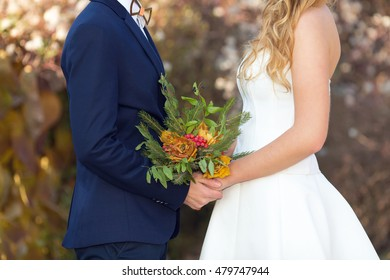 Close up hands bride and groom outdoors. Autumn wedding day and bridal bouquet. Marriage.