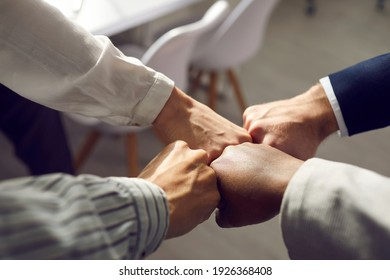 Close up of hands of business partners folding fists together as a symbol of unity. Four people bumping their fists together in an office at a meeting. Concept of trust, friendship and cooperation.
