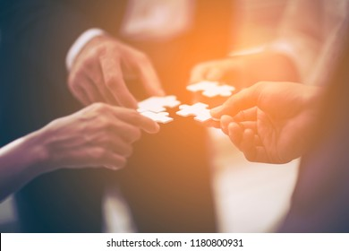 close up hands of business people team or partnership holding jigsaw puzzle piece connecting and solving puzzle for start investment expansion or new project. Trust and team success unity concept.