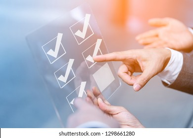Close up hands businessman doing checking mark on checklist  on virtual touch screen. Customer service evaluation and technology customer support concept,mail,phone,email