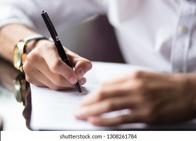 Close up of the hands of a businessman in a shirt signing or writing a document on a sheet of white paper using a nibbed fountain pen