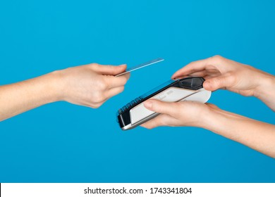 Close up hands of cashier holding credit card reader and client paying trought contactless credi card. Customer paying with NFC technology isolated on blue background.