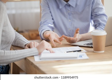 Close up hands of Caucasian millennial women sitting at the desk. Advisor interviewing new candidate, girls colleague coworking together at business meeting or client visit real estate agency office