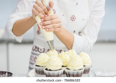 Close up hands of the chef with confectionery bag squeezing  cream on cupcakes