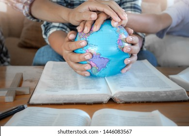 Close up hands of christian group praying for globe and people around the world on wooden table with bible.
