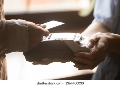 Close up hands client pay bill in cafe or shop hold contactless credit card with NFC near field communication, cashier using reader machine people make easy cashless deal transaction payment concept