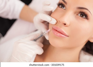 Close up of hands of cosmetologist making botox injection in female lips. She is holding syringe. The young beautiful woman is receiving procedure with enjoyment