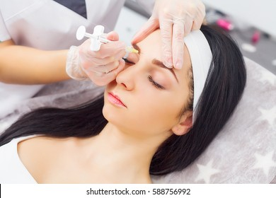 Close up of hands of cosmetologist making botox injection in female lips. She is holding syringe. The young beautiful woman is receiving procedure with enjoyment.