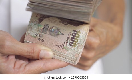 Close up hands counting of thousansds Thai baht money.Close up Human counting Thai banknote, richman count and holding hundred. Baht bills on table