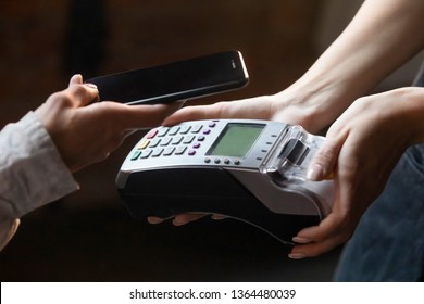 Close up hands customer cashier make transaction holding terminal and mobile phone cellphone client paying using NFC near field communication, easy usage of two electronic devices modern tech concept