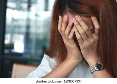 Close up hands of depressed stressed young Asian woman covering face