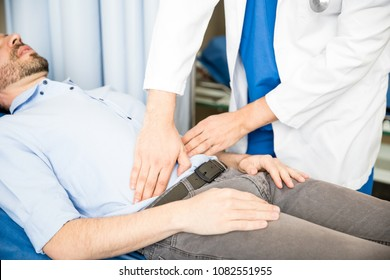 Close up of hands of the doctor touching the abdomen of a patient in the emergency room