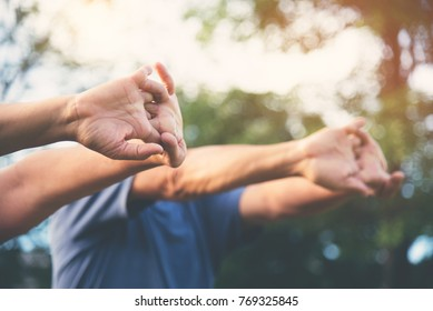 Close up hands of elderly people stretching before exercise at park on holidays. Happy Asian Senior enjoying workout at outdoor with sunlight. Good Health, Wellness.