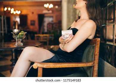 close up hands of elegant beautiful woman sitting in vintage cafe in black velvet dress holding little golden purse in hand, rich stylish lady, elegant fashion trendy accessories