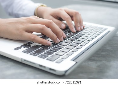 Close up hands of an employee is using a computer notebook by typing on keyboard at the desk.