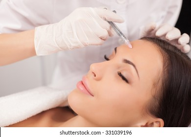 Close up of hands of expert beautician injecting botox in female forehead. The woman closed her eyes with joy. She is gently smiling