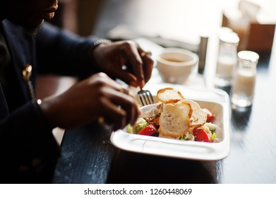 Close up hands of fashionable african american man in suit sitting at cafe and eating salad.