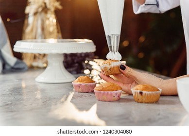 Close up hands of the female chef with confectionery bag squeezing cream on cupcakes.