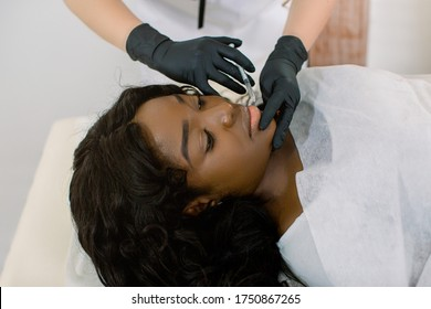 Close up of hands of female cosmetologist making botox injection in female lips, holding syringe. The young beautiful African American woman relaxing on the couch. Aesthetic surgery, cosmetology