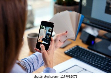 Close up hands of female designer in office working with colour samples. Woman at workplace makes a photo of color palette on smartphone.