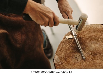Close up of hands of female jewelry maker bending a silver blank on road using a mallet hammer on workbench. Goldsmith making a ring in workshop.