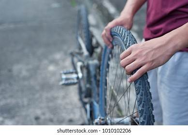 Close up of hands fixing an old bicycle tire.