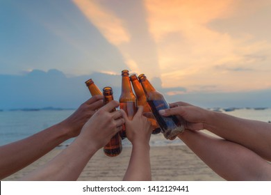 Close up of hands of friends clanging bottles of beer together and celebrating on holiday in party at the beach or sea in summer at sunset time