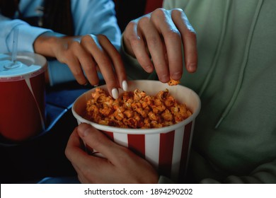 Close up of hands of a girl and a guy taking popcorn out of basket while watching movie together at the cinema. Entertainment and people concept. Horizontal shot