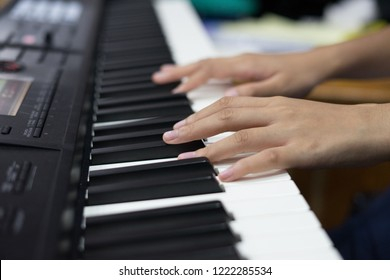 close up of the hands of girl on the keyboard of the piano